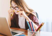Dziewczyna siedząca przed laptopem i gryząca ołówek.