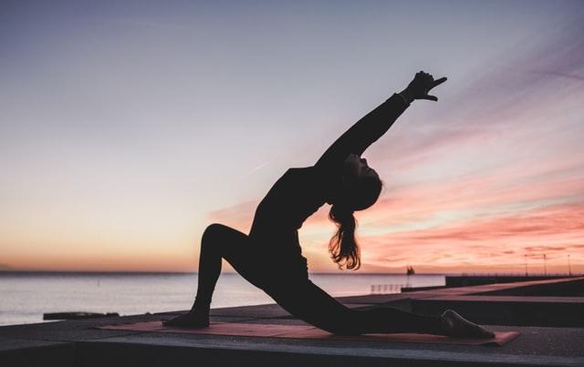 Dziewczyna ćwicząca jogę na plaży o zachodzie słońca.