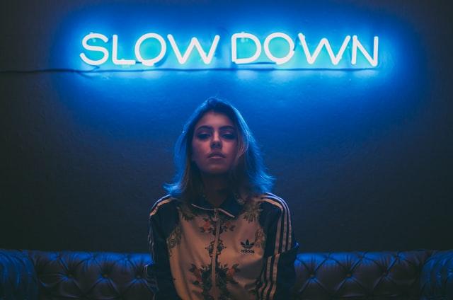 """Dziewczyna na tle niebieskiej ściany z neonowym napisem """"slow down"""""""