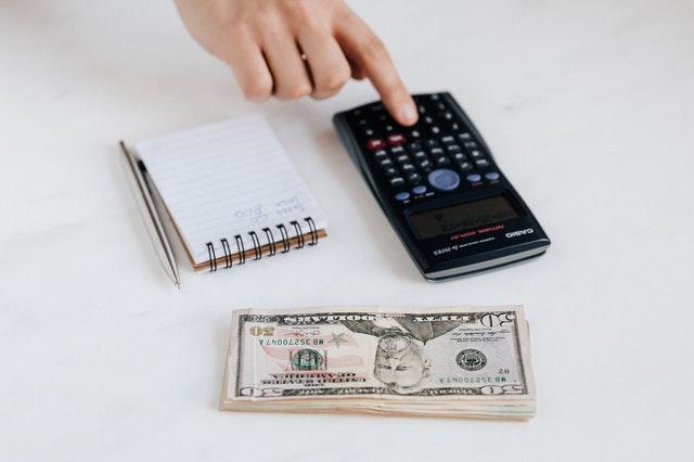 Pieniądze, kalkulator i notes na biurku.