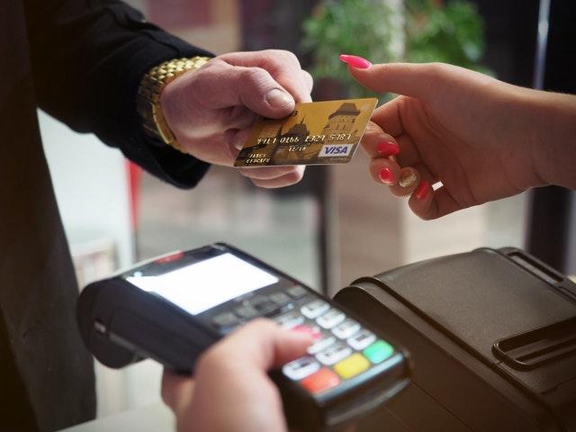 Mężczyzna płacący kartą płatniczą i terminal.