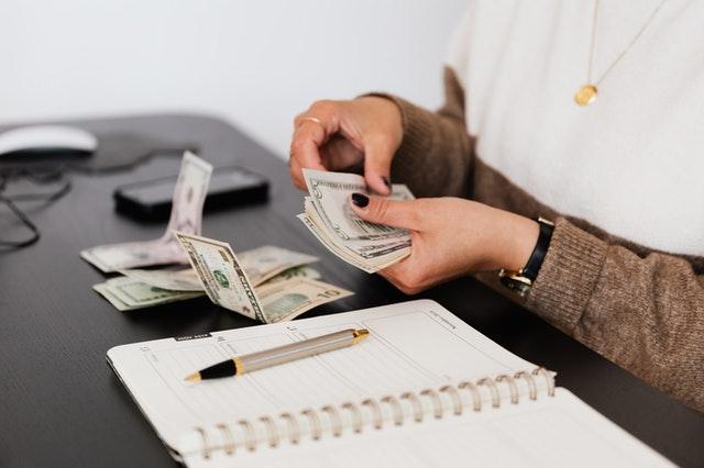 Kobieta przeliczająca pieniądze.