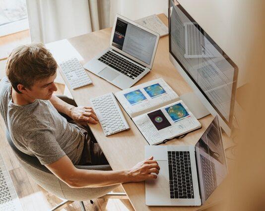 Mężczyzna siedzący przy biurku z 2 laptopami, dodatkowym monitorem i papierami