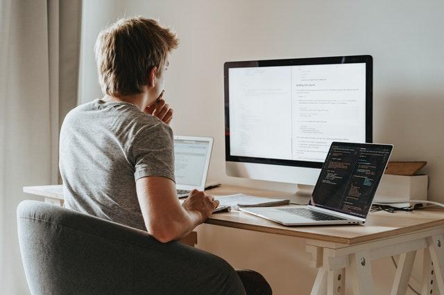 Mężczyzna siedzący przy biurku z otwartym laptopem i monitorem.