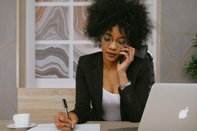 Dziewczyna pracująca zdalnie z laptopem i telefonem przy uchu.