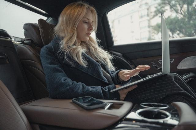 Dziewczyna w aucie pracująca na laptopie.